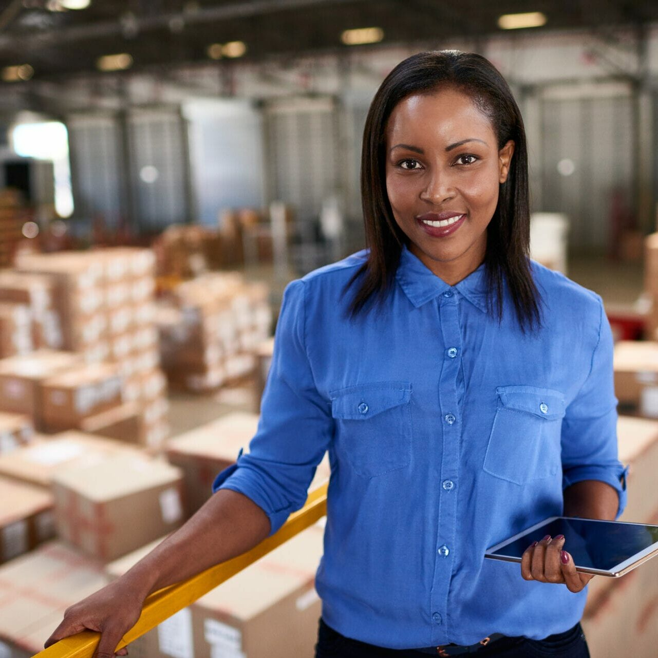 Portrait of a smiling worker holding a digital tablet while standing in a large warehouse full of boxes